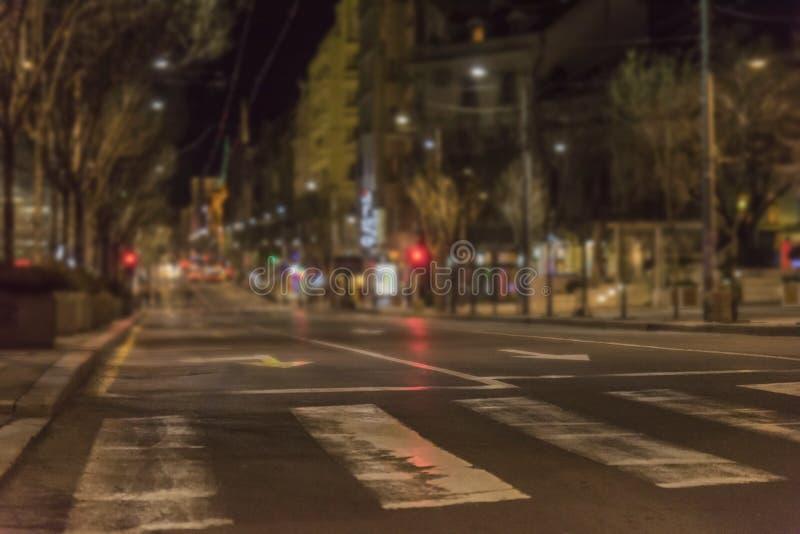 Nachtscène met voetganger in voorgrond en de verlichte bouw royalty-vrije stock afbeeldingen