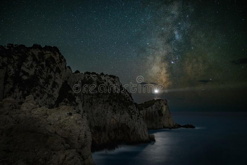 Nachtscène van vuurtoren onder melkachtige manierhemel stock foto
