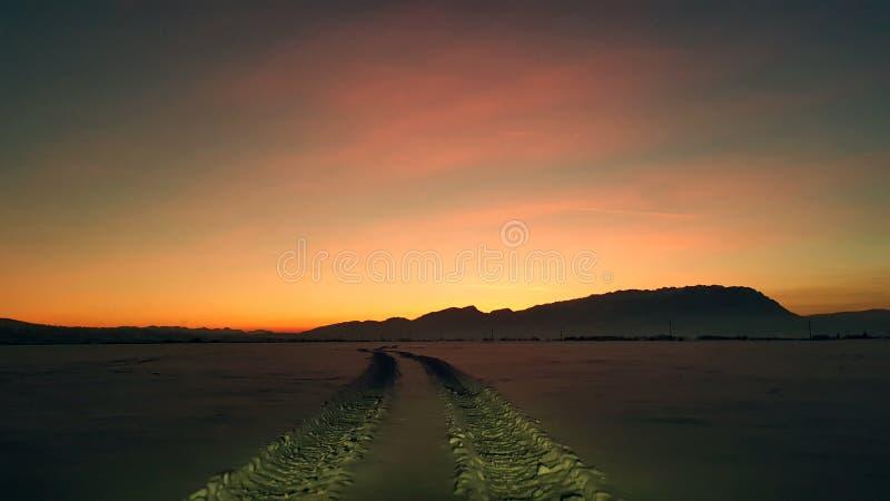 Nachtschneebahn schleppt - Sonnenuntergang stockfotos