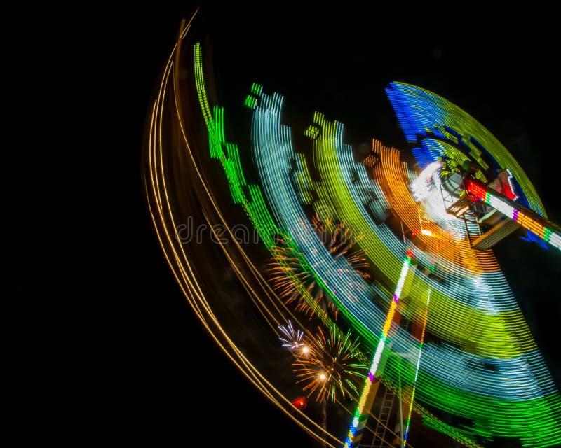 Nachtschot van een Carnaval-rit in motie met vuurwerk stock afbeeldingen