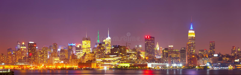 Nachtskylinepanorama New York City, USA buntes stockbilder