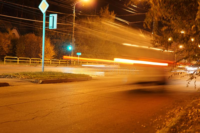 Nachtstadtverkehr verwischte die Lichtscheinwerferstraßenbaumherbst-Lichtlünetten, die Hintergrund des Autolaubbusch-grellen Glan lizenzfreie stockfotografie