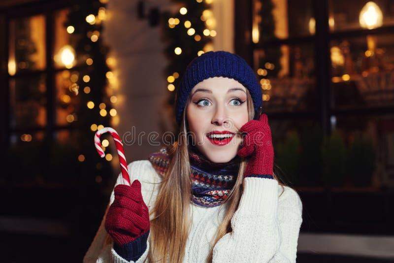 Nachtstraßenporträt der lächelnden schönen jungen Frau, die am Handy spricht und beiseite schaut Tragender Klassiker Dame lizenzfreies stockbild