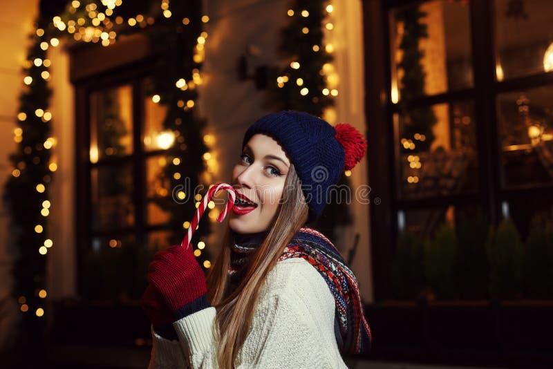Nachtstraßenporträt einer lächelnden schönen beißenden Zuckerstange der jungen Frau Dame, die klassischer Winter gestrickte Kleid lizenzfreies stockfoto