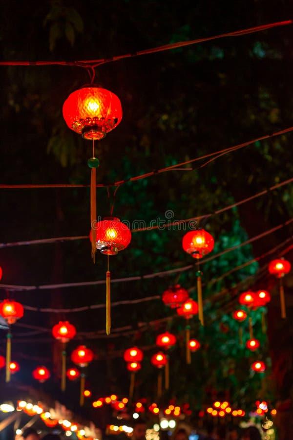 Nachtstraat die met rode Chinese lantaarns over de hoofden van mensen wordt verfraaid stock foto's