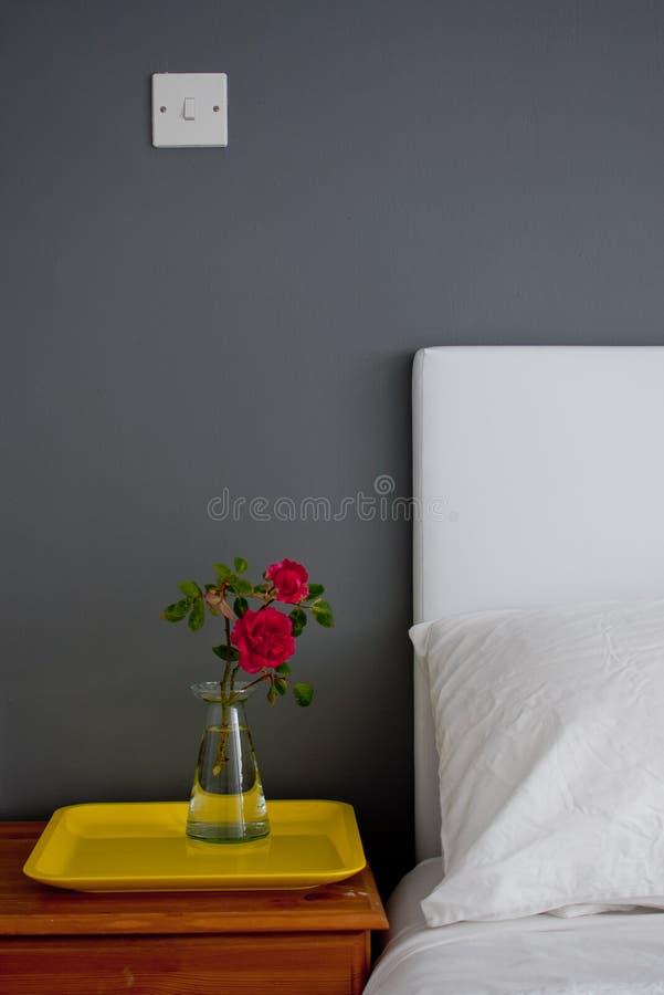 Nachttisch mit einer Rose und einem Behälter lizenzfreie stockfotografie