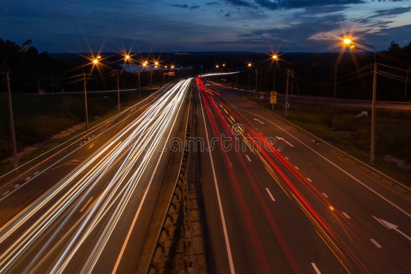 Nachtverkehrs-Straßenlandstraße mit Autolichtern stockbilder