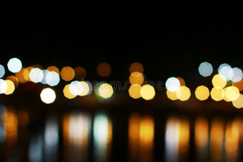 Nachtverwischte helle bokeh Unschärfe Fluss mit Reflex im Wasser lizenzfreie stockfotos