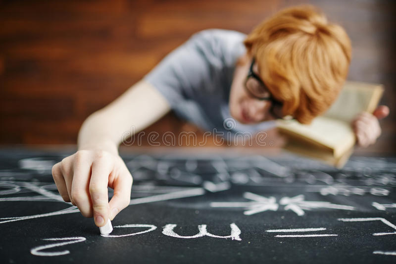 Nachwuchswissenschaftler Writing auf Tafel in der Klasse lizenzfreie stockbilder
