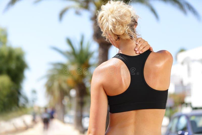 Nackenschmerzen - Sportläuferfrau mit Rückenverletzung stockfoto