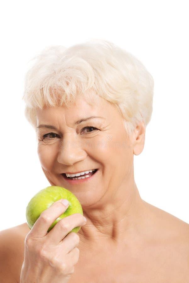 Nackte Holding und Apfel der alten Frau. stockbilder