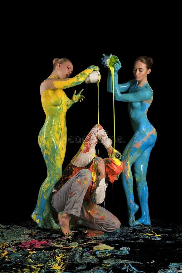 Nackte Mädchen, die Farbe auf einem Mann sitzt auf Boden gießen stockfotografie