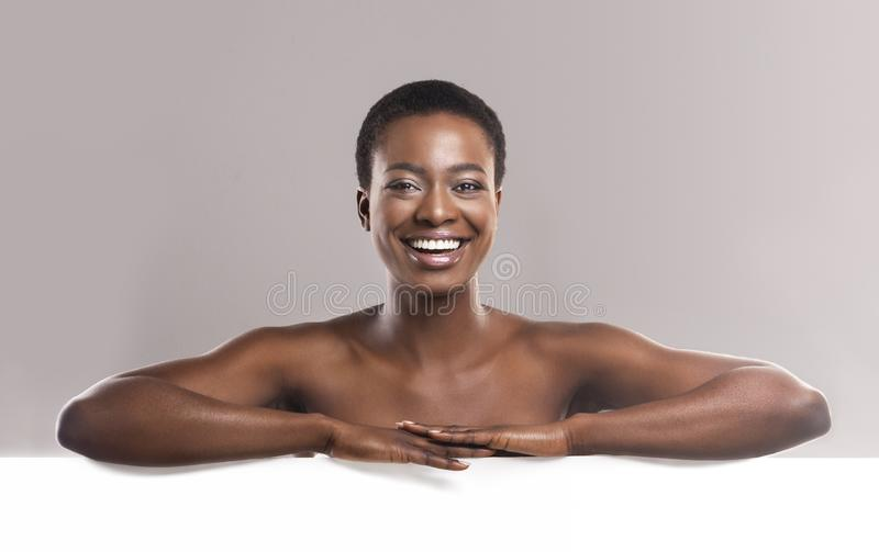 Nackter Afroamerikanermann, der am weißen leeren Brett sich lehnt lizenzfreies stockfoto