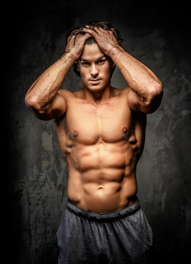 Nackter Bodybuilder, der seinen Kopf hält lizenzfreies stockbild