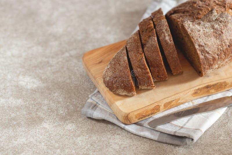 Naco cortado fresco do pão de centeio no fundo de madeira da placa de corte com guardanapo e faca foto de stock