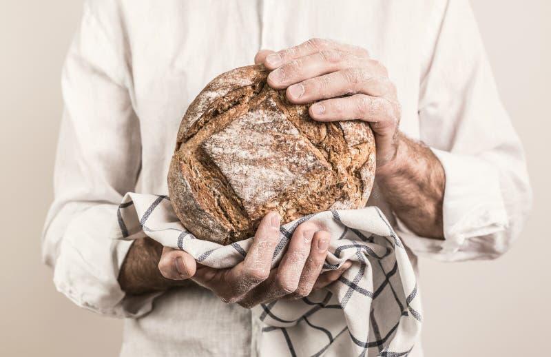 Naco de pão duro rústico nas mãos do ` s do homem do padeiro fotos de stock