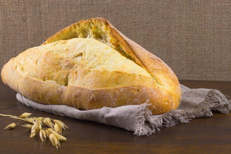 Naco de pão e um ramo da aveia na tabela fotografia de stock