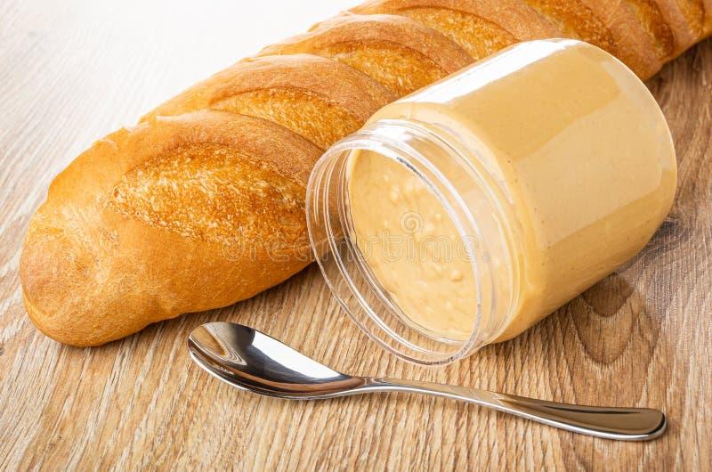 Naco de pão, frasco virado com manteiga de amendoim, colher na tabela de madeira fotografia de stock