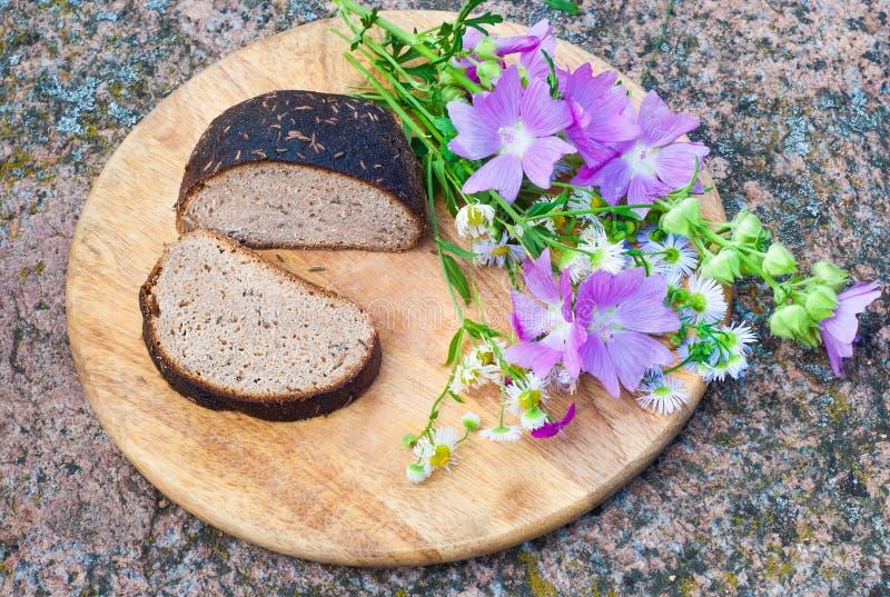 Naco do pão de centeio com sementes de alcaravia e as flores selvagens foto de stock