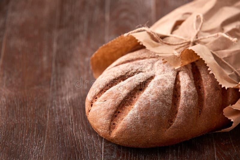Naco do pão de centeio no saco de papel na tabela de madeira Fundo da padaria fotografia de stock royalty free