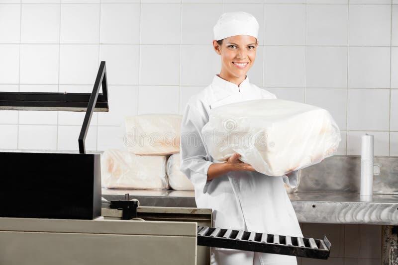 Naco fêmea de Holding Packed Bread do padeiro imagens de stock