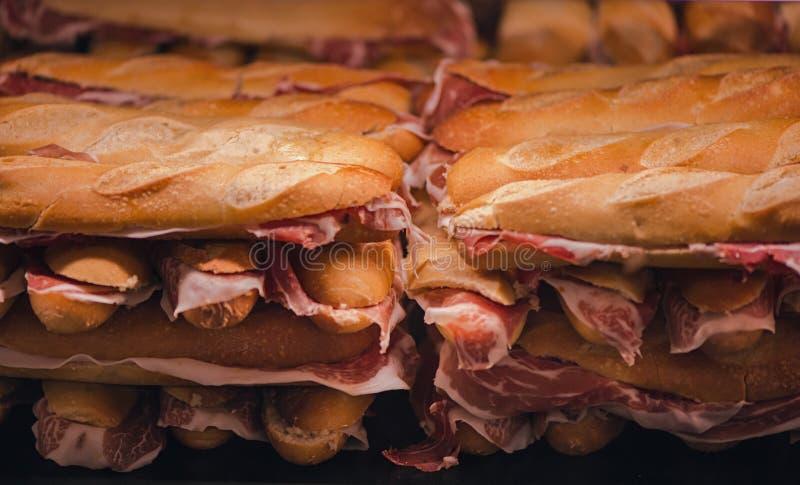 Naco francês com jamon espanhol Presunto espanhol tradicional Fatias finas do jamon de Iberico entre de duas partes foto de stock