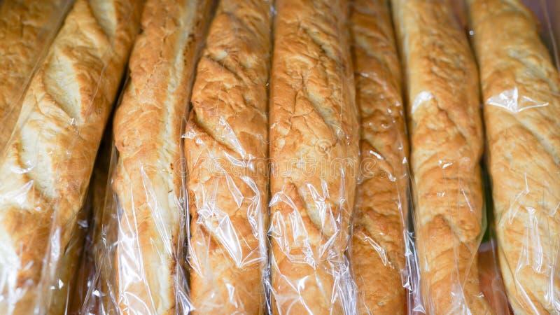 Naco longo dos baguettes frescos em uma cesta de vime em uma loja da padaria fotos de stock royalty free