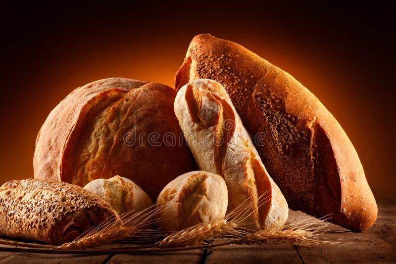 Nacos de pão e de orelhas do trigo fotos de stock royalty free
