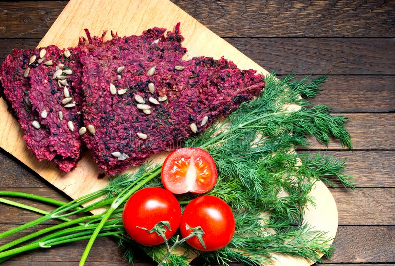Nacos, tomates e aneto secos desidratados do pão do vegetariano na placa da cozinha na tabela de madeira imagens de stock royalty free