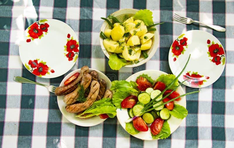Naczynia na stole - warzywa, grule, Bawarskie kiełbasy obraz royalty free