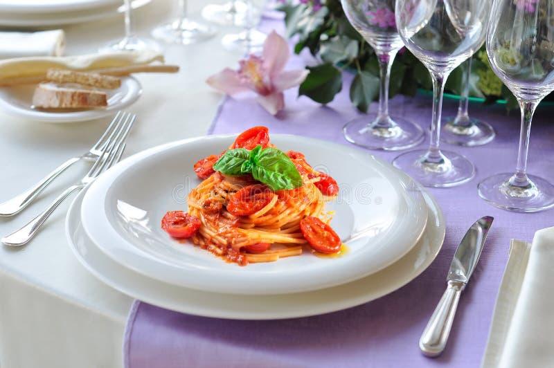 Naczynie spaghetti basil na kłaść stole i pomidor zdjęcia royalty free