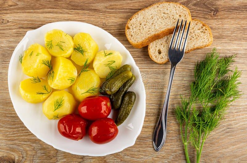 Naczynie z piec grulą, marynowani pomidory, korniszony, koper, chleb, rozwidlenie, wiązka koper na stole Odg?rny widok zdjęcie royalty free