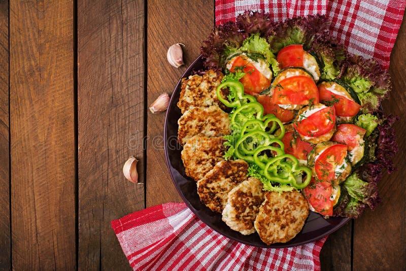 Naczynie z przekąską smażący zucchini z pomidorami i tłustoszowatymi kurczaków cutlets z zucchini obraz royalty free