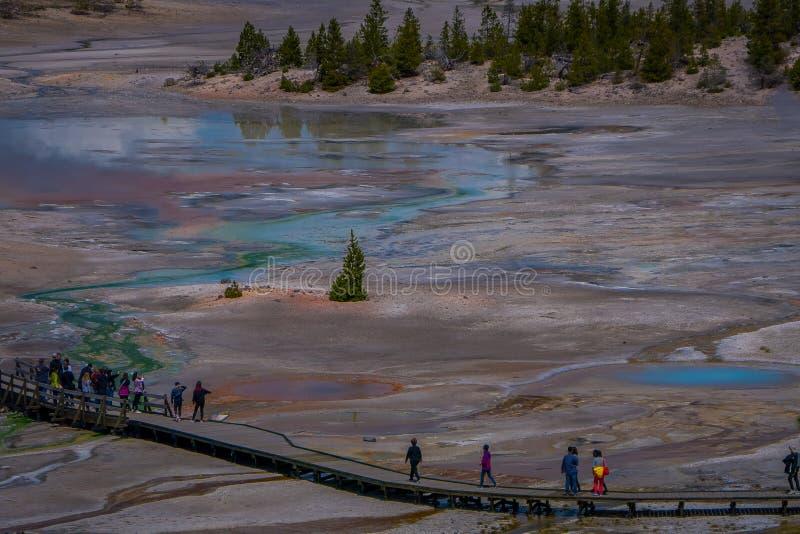 Nad widok ludzie chodzi w boardwalk wśród basenów i gejzerów Jałowy barwiący basen Porcelana basen zdjęcia royalty free