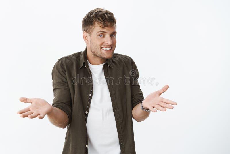 Nada que você pode fazer agora Retrato do homem considerável frio descuidado e unbothered com shrugging relaxado do sorriso confu fotografia de stock