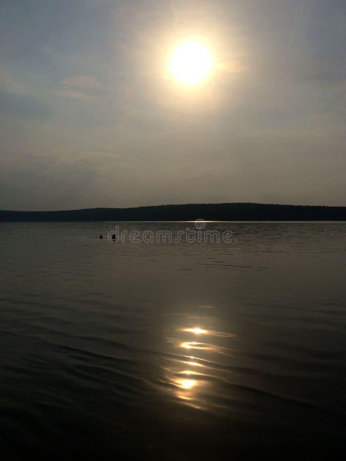 Nadada de dos personas en el lago durante puesta del sol Ural, Rusia fotos de archivo libres de regalías