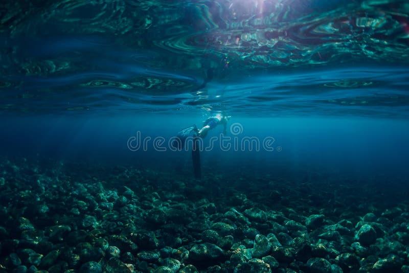 Nadada de Freediver no oceano, na foto subaquática com luz solar e na profundidade foto de stock royalty free
