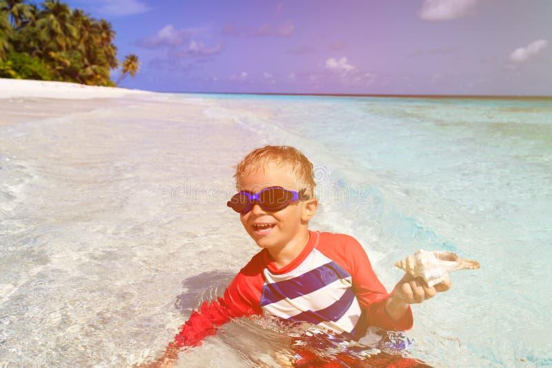 Nadada del niño pequeño con la cáscara en la playa fotografía de archivo