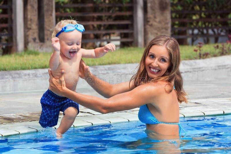 Nadada feliz da criança com a mulher bonita na associação fotos de stock