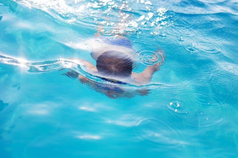 Nadada nova do menino subaquática na piscina imagem de stock