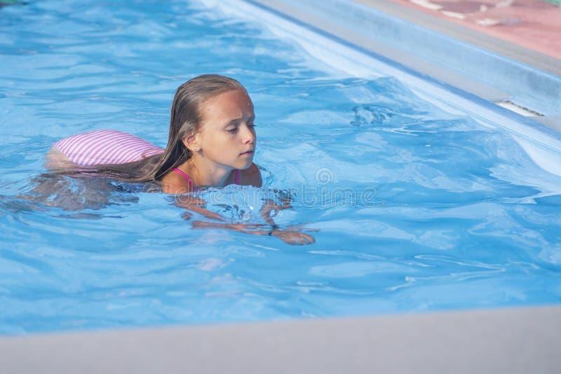 Nadadas bonitas na associação, menina bonito da menina na associação no dia ensolarado foto de stock