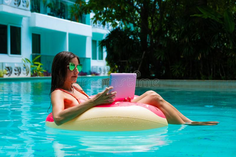 Nadadas da jovem mulher no mar em um c?rculo nadador Menina que descansa na associa??o em um c?rculo infl?vel com um computador,  fotos de stock