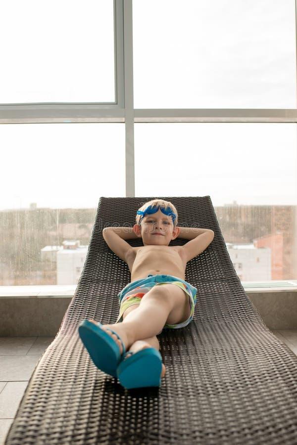 Nadador bonito relaxado na cadeira de sala de estar imagens de stock