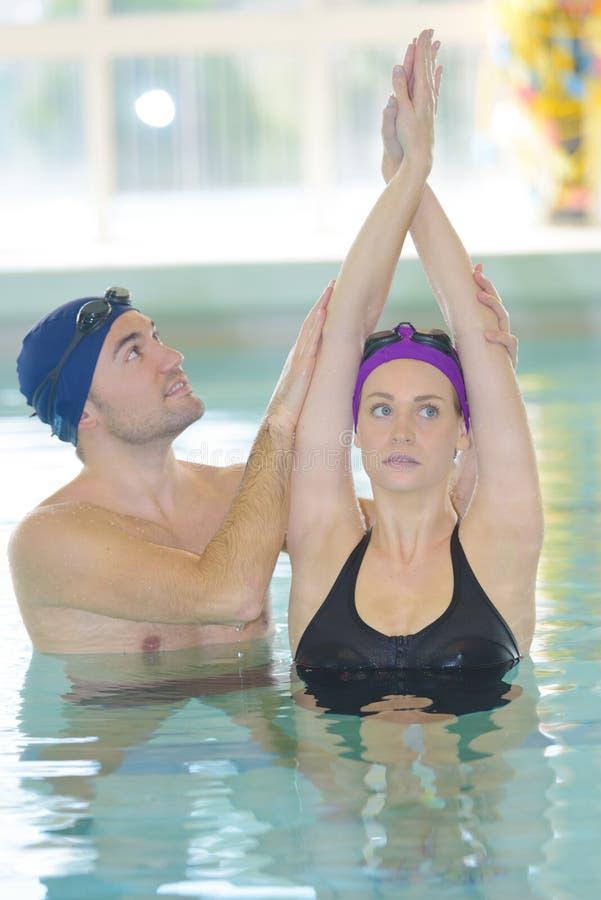 Nadador con la novia dentro de la piscina fotografía de archivo libre de regalías