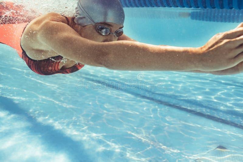 Nadador de sexo femenino que se desliza en piscina imagenes de archivo