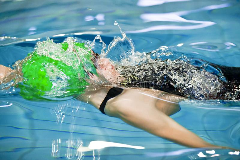 Nadador do homem de Oung com rastejamento dianteiro das nadadas verdes do tampão ou curso de rastejamento dianteiro em uma piscin fotos de stock
