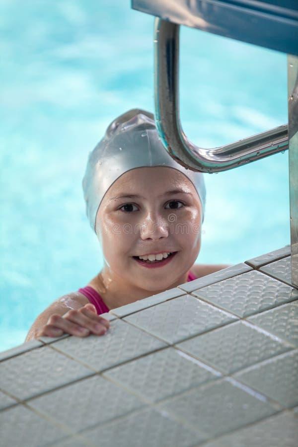 Nadador feliz y sonriente de la muchacha que mira la cámara mientras que se coloca en el agujero de riego imagen de archivo