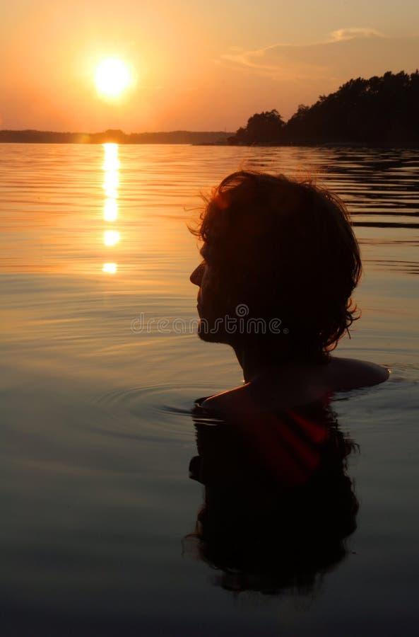 Nadador no por do sol no mar Báltico, Suécia imagem de stock royalty free