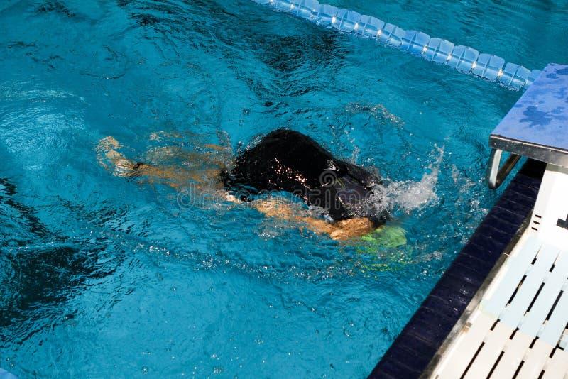 Nadador que da vuelta detrás en el borde de una encuesta imagenes de archivo