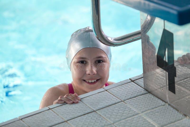 Nadador sonriente de la chica joven en casquillo gris en la piscina cerca de un bloque el comenzar imagenes de archivo